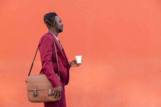 Eleganter afrikanischer geschäftsmann in einem anzug mit aktentasche, der einen kaffee in der hand vor einem roten hintergrund hält, platz für text kopieren