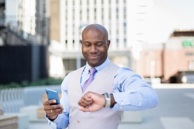 Eleganter afroamerikanischer geschäftsmann, der die zeit auf seiner uhr beim lächeln betrachtet.