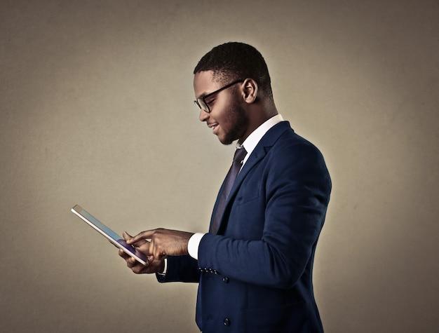 Eleganter afromann, der eine tablette verwendet