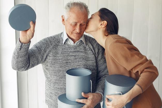 Eleganter alter mann, der zu hause mit seiner enkelin steht