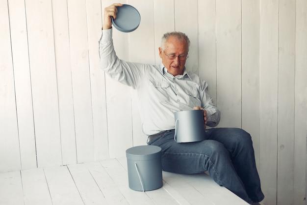 Eleganter alter mann, der zu hause mit weihnachtsgeschenken sitzt