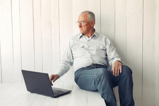 Eleganter alter mann, der zu hause sitzt und einen laptop verwendet
