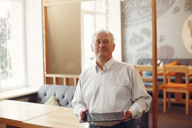 Eleganter alter mann in einem café mit einem laptop