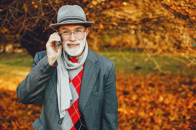 Eleganter alter mann in einem sonnigen herbstpark