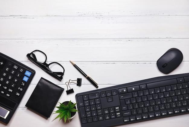Eleganter arbeitsbereich mit geschäftszubehör auf weißem hintergrund mit copyspace. office-desktop. schreibtisch mit tastatur, büromaterial, bleistift, grünes blatt auf holztisch. kreatives flaches laienfoto