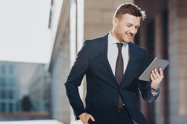 Eleganter attraktiver mannexekutivmanager hält moderne digitale tablette