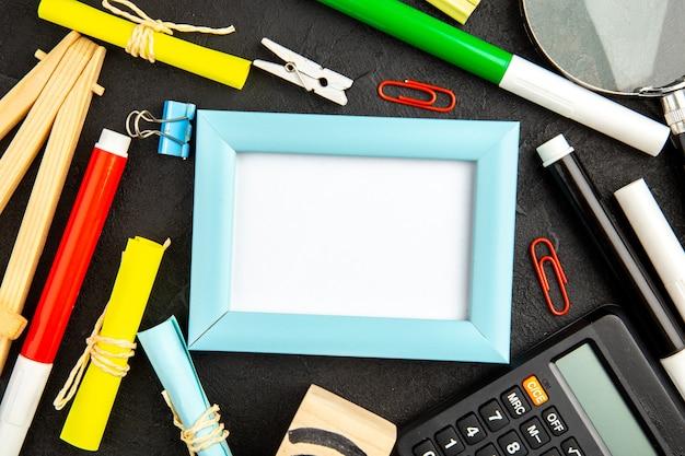 Eleganter bilderrahmen der draufsicht mit bleistiften und taschenrechner auf einer dunklen oberfläche präsentieren farbliebesfamilienfoto-geschenkporträt