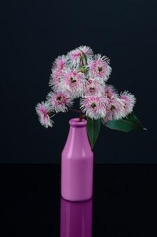 Eleganter blumenstrauß von weißen rosa eukalyptusblumen in einer purpurroten flasche