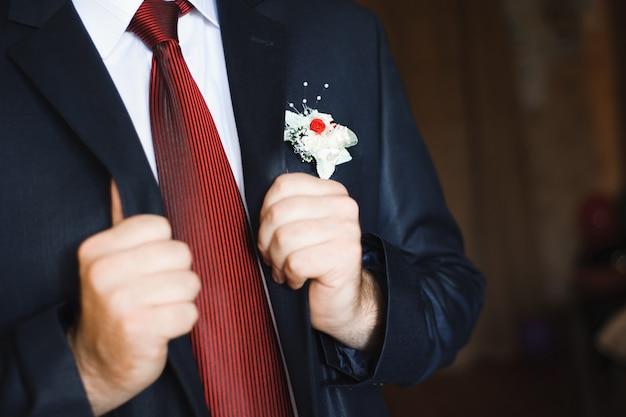 Eleganter bräutigam, der in einem hochzeitsanzug ankleidet