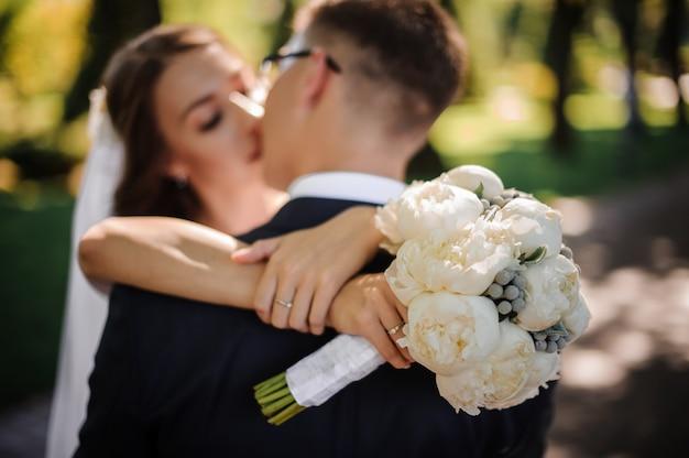 Eleganter bräutigam in einem festlichen anzug küsst eine schöne braut
