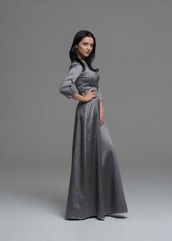 Eleganter brunette im sexy kleid, das im studio aufwirft