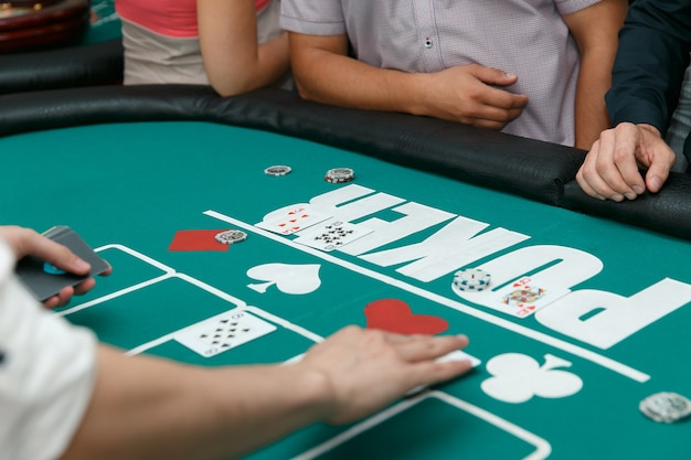Eleganter croupier beim poker legt karten mit chips auf einen tisch.