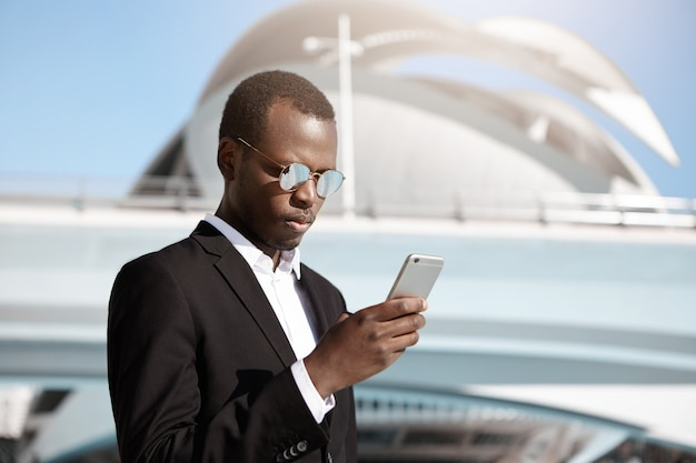 Eleganter ernsthafter afroamerikanischer angestellter auf geschäftsreise, die e-mail auf mobiltelefon prüft, außerhalb des modernen gebäudes des flughafens stehend, während an sonnigem sommertag draußen auf taxiwagen wartet