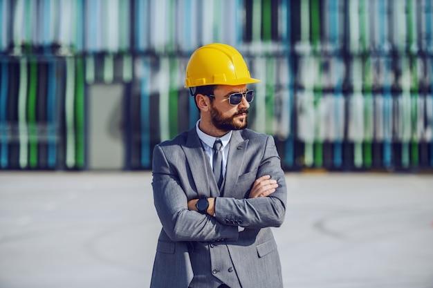 Eleganter ernsthafter kaukasischer bärtiger geschäftsmann im anzug, mit sonnenbrille und helm auf dem kopf stehend auf der baustelle mit verschränkten armen und überwachung der arbeiten.