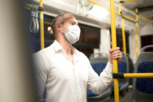 Eleganter erwachsener männlicher reitbus mit chirurgischer maske