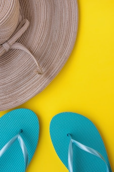 Eleganter frauen-strohhut mit bogen-blauen pantoffeln auf gelbem hintergrund