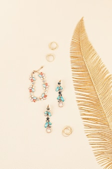 Eleganter frauenschmuck mit goldenem blatt über beiger lederwand. online-juweliergeschäft, geschenkideen, beaty-blog, elegantes look-konzept. minimale flache lage