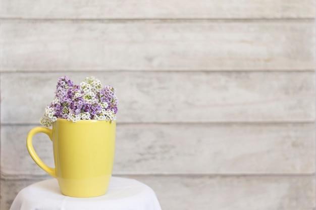 Eleganter gelber becher mit blumen und holzuntergrund