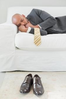 Eleganter geschäftsmann, der auf sofa schläft