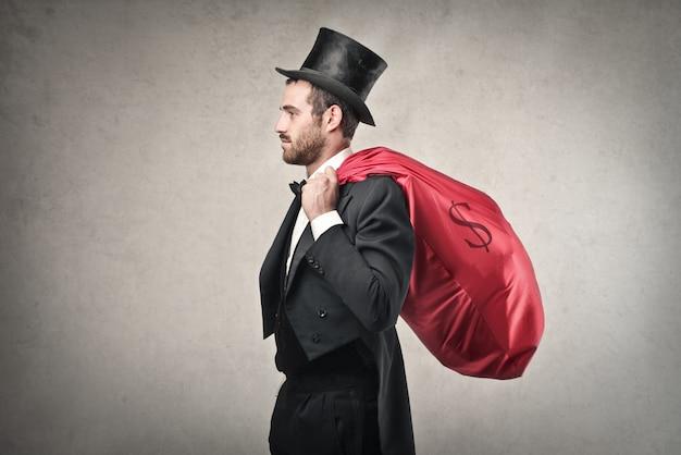 Eleganter geschäftsmann, der eine große rote tasche hält