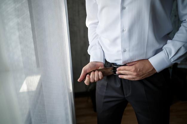 Eleganter geschäftsmann, der einen gürtel an seiner hose befestigt, trägt ein weißes hemd
