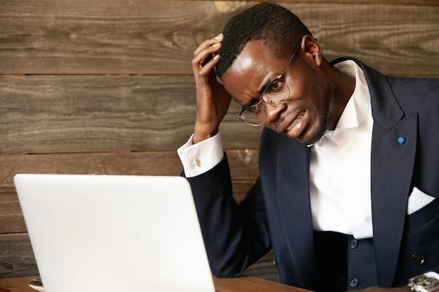 Eleganter geschäftsmann, der im café mit laptop sitzt