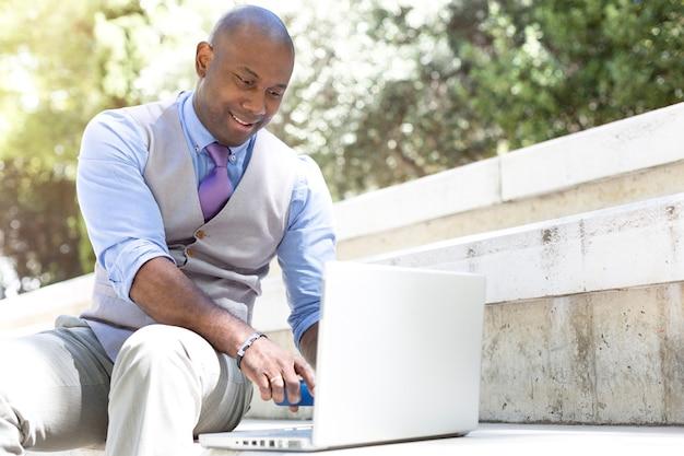 Eleganter geschäftsmann, der mit seinem laptop auf der straße arbeitet.