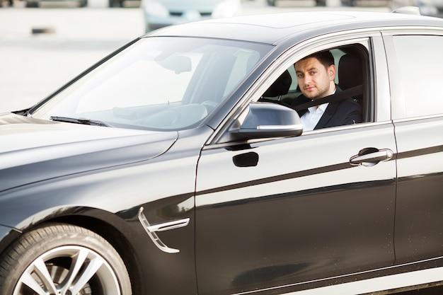 Eleganter geschäftsmann kleidete in der klage an, die den sicheren gurt befestigt, bevor er sein auto fuhr