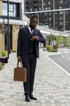 Eleganter geschäftsmann mit handtasche, der beim stehen auf der straße auf die armbanduhr schaut