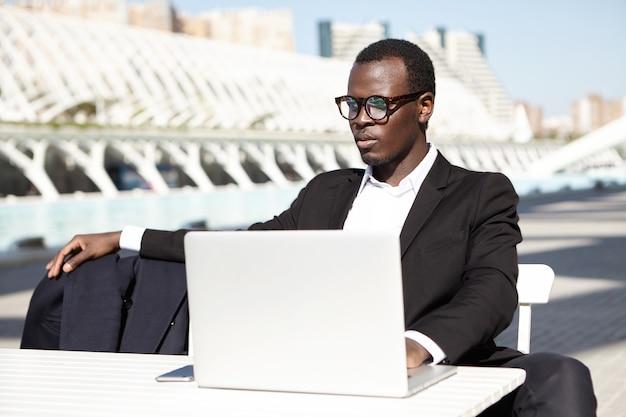 Eleganter geschäftsmann mit laptop im freien