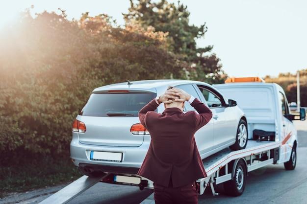 Eleganter geschäftsmann mittleren alters, der abschleppdienst für hilfe bei autounfällen auf der straße verwendet. konzept der pannenhilfe.