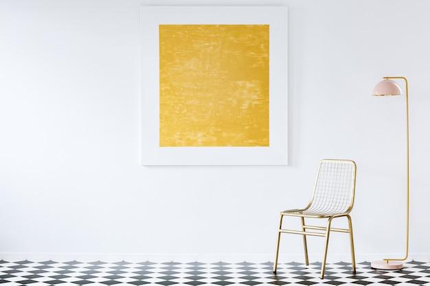 Eleganter goldener stuhl und stehlampe in einem luxuriösen wohnzimmer mit einem modernen abstrakten gemälde an einer leeren weißen wand