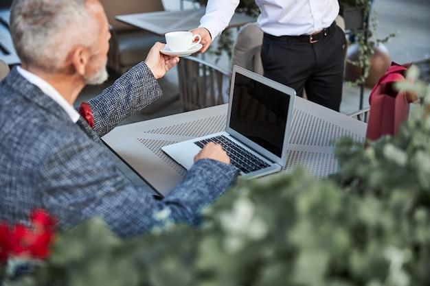 Eleganter grauhaariger mann, der eine tasse kaffee von einem kellner erhält, während er im café am laptop arbeitet