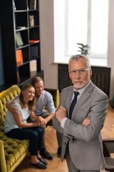 Eleganter, gut aussehender psychoanalytiker, der während der therapiesitzung in seinem büro neben einem lächelnden ehepaar steht