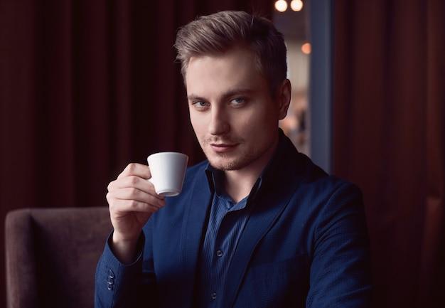 Eleganter gutaussehender mann mit tasse kaffee
