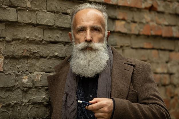 Eleganter herr mit langem bart, der draußen raucht.