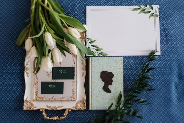 Eleganter hochzeitsstrauß aus frischen naturblumen und grün mit buch