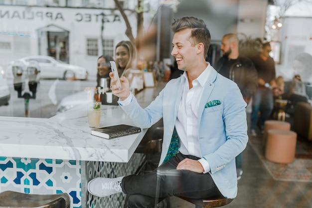 Eleganter junge, der in einer bar plaudert auf dem mobile sitzt