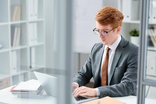 Eleganter junger anwalt, der fragen der benutzer online beantwortet, während er vor laptop im büro sitzt