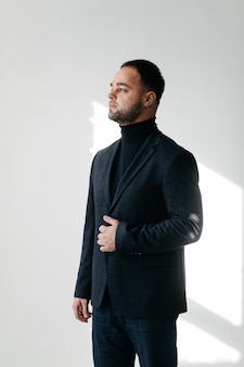 Eleganter junger gutaussehender mann im klassischen schwarzen kostüm. studiomodeporträt.