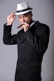 Eleganter junger gutaussehender mann in einem anzug mit einer zigarre.