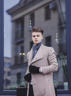 Eleganter junger hübscher geschäftsmann, der mantel und handschuhe trägt