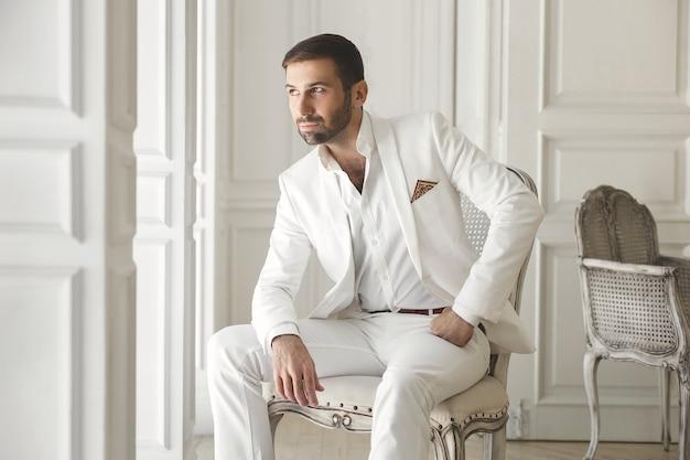 Eleganter junger hübscher mann mit einem bart in einem weißen klassischen anzug.