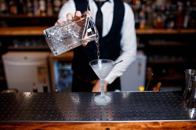 Eleganter junger männlicher kellner bereitet ein köstliches cocktail zu