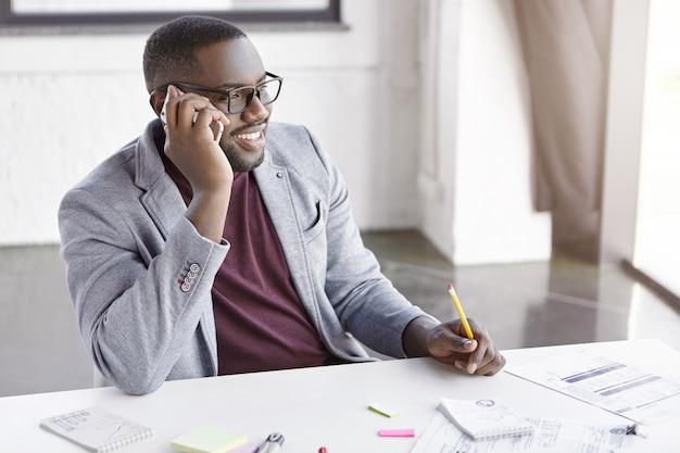 Eleganter junger mann, der im büro arbeitet