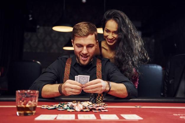 Eleganter junger mann mit frau vor ihm sitzt und feiert vitory im kasino, indem er pokerspiel spielt