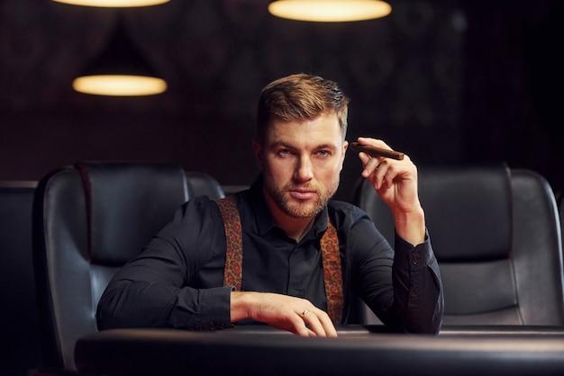 Eleganter junger mann mit zigarette sitzt im kasino und spielt pokerspiel