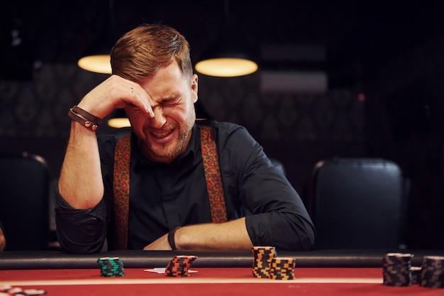 Eleganter junger mann sitzt im kasino und fühlt sich schlecht, weil er pokerspiel verliert