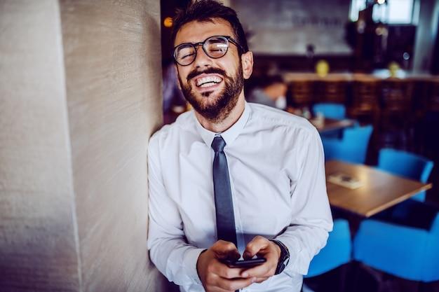 Eleganter kaukasischer bärtiger gutaussehender geschäftsmann in hemd, krawatte und mit brille, die an wand im café lehnt und smartphone zum lesen oder senden der nachricht verwendet