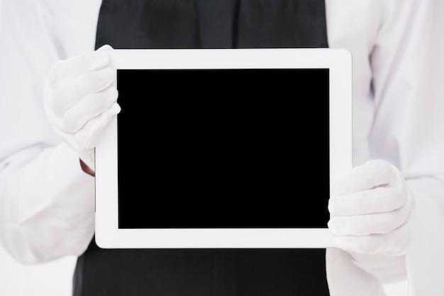 Eleganter kellner, der tablettenmodell hält